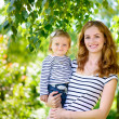 Beautiful young mother and cute daughter smiling at nature  — Stock Photo