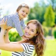 Young mother and cute daughter with blue eyes playing at park — Stock Photo