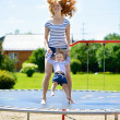 Young mother and little daughter bouncing on trampoline — Stock Photo
