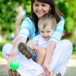 Young mother with her son in park — Stock Photo