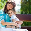 Young mother with her son in park — Stock Photo #27212693