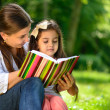 Happy latino family reading book — Stock Photo #28451245