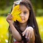 Cute hispanic girl hiding over yellow leaf — Stock Photo #28451637