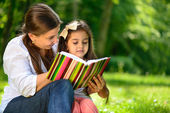 Happy latino family reading book — Stock Photo
