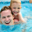 Young father and little son swimming in pool — Stock Photo #28617473