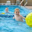 Happy father and son playing with ball in swimming pool — Stock Photo