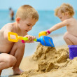 Two children playing with sand at ocean beach — Stock Photo #28617683