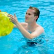 Young man with ball in swimming pool — Stock Photo