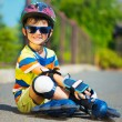 Cute little boy in sunglasses with rollers — Stock Photo