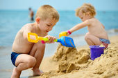 Two children playing with sand at ocean beach — Stock Photo
