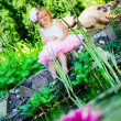 Stock Photo: Llittle girl in ballerina tutu sitting at pond