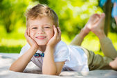 Cute little boy with butterfly lying on green grass — Stock Photo