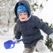 Little boy with shovel playing in snow — Stok fotoğraf