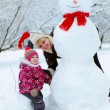 Grandmother with granddaughter playing in snow — Stock Photo