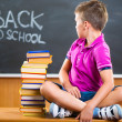 Cute school boy sitting with books in classroom — Stock Photo #30751279