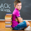Cute school boy sitting with books in classroom — Stock Photo