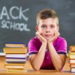 Cute pupil with books in classroom — Stock Photo