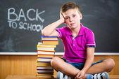Söt skola pojke sitter med böcker i klassrummet — Stockfoto