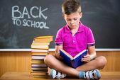 Cute school boy reading book in classroom — Stock Photo
