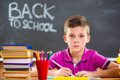 Cute school boy studying in classroom — Stock Photo