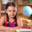 Cute hispanic girl in classroom at school — Stockfoto