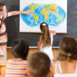 Young teacher at geography lesson — Stock Photo