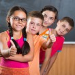 Four smiling schoolchildren standing in classroom — Stock Photo