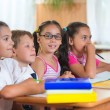 Stock Photo: Four diligent pupils studying at classroom