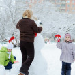 Mother and children building snowman — Stock Photo