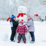Children building snowman in garden — Stock Photo
