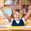 Successful schoolboy with hands up sitting at desk — Stock Photo