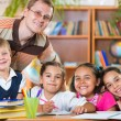 Group of pupils in classroom with teacher  — Stock Photo