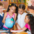 Portrait of pupils looking at globe with their teacher — Stock Photo #31238447