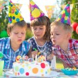 Kids at birthday party blowing candles on cake — Stock Photo