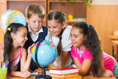 Portrait of cute schoolchildren looking at globe — Stock Photo