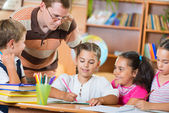Portrait of diligent schoolkids and their teacher at lesson — Stock Photo