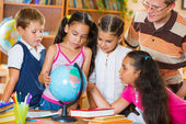 Portrait of pupils looking at globe with their teacher — Stock Photo