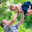 Young happy dad playfully tosses his little daughter — Stock Photo