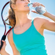 Pretty sportswoman with racket on shoulders — Stock Photo