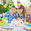 Stock Photo: Kids blowing candles on cake at birthday party