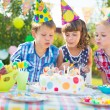 Kids blowing candles on cake at birthday party — Stock Photo #32128821