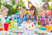 Kids blowing candles on cake at birthday party — Стоковое фото