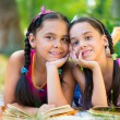 Stock Photo: Portrait of two hispanic sisters reading in park
