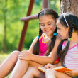 Portrait of two happy sisters reading in the park — Stock Photo