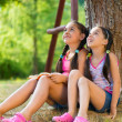 Hispanic sisters sitting under the tree and talking — Stock Photo #32130455