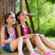 Hispanic sisters sitting under the tree and talking — Stock Photo