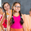 Four schoolchildren standing in classroom against blackboard — Stock Photo