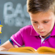 Cute schoolboy reading in classroom — Stock Photo