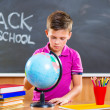 Cute schoolboy looking on globe — Stock Photo #32131673