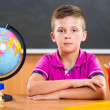 Stock Photo: Cute diligent boy sitting in classroom